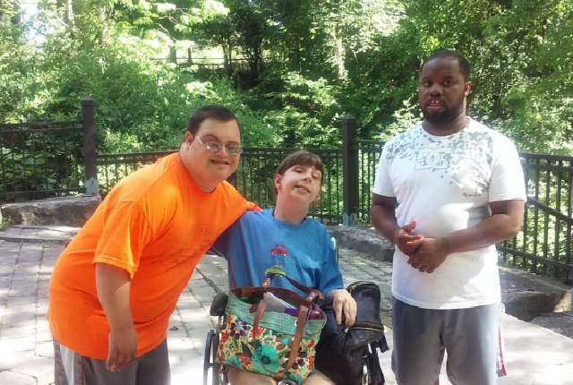 two man with a girl in a wheelchair